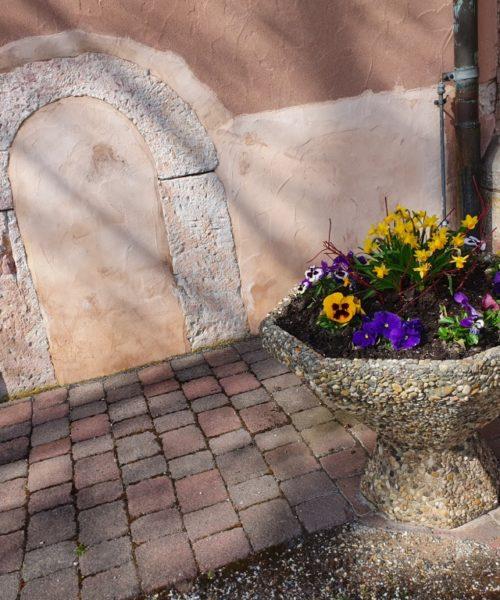 Blumenschale vor Kirche mit historischem Eingang